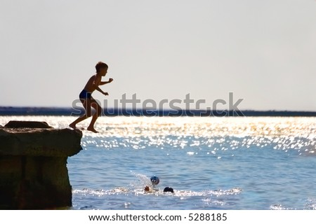 The boy jumping in water from a pier - stock photo