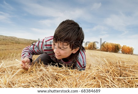 The boy jumps on a haystack - stock photo