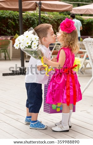 The boy kid gives flowers to girl child on birthday. Little adorable girl celebrating 3 years birthday. Childhood. - stock photo