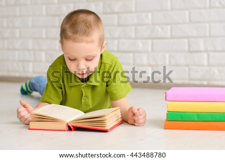 The boy lay on the floor and reading a book near pile of books, against a white brick wall