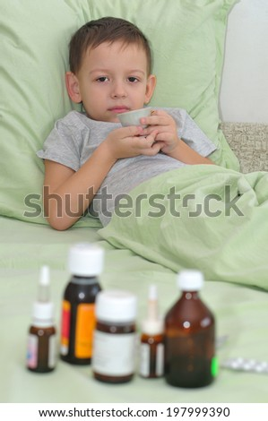 The boy lies in pastels and do not want to drink the syrup - stock photo