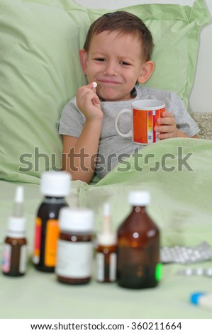 The boy lies in pastels and do not want to take medicine - stock photo