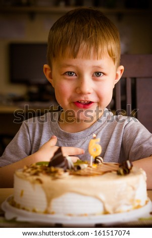 The boy looks at the birthday cake - stock photo