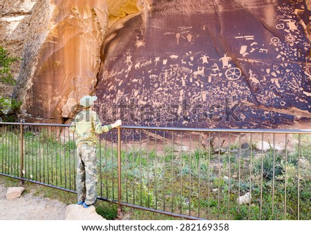 The boy looks at the Newspaper Rock.  State Historic Monument is a Utah  - stock photo