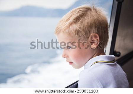 The boy looks at the sea from the deck of the ship. Boy with blond hair in a good mood on the deck, watching the sea.Sea voyage. - stock photo