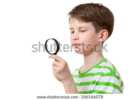 the boy looks through a magnifying glass - stock photo