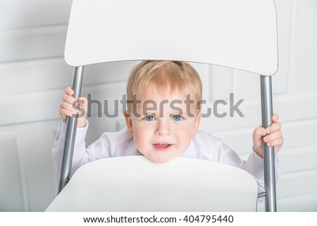 The boy looks through the chair