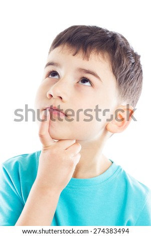 The boy lost in thought, looking up, his finger in chin - stock photo