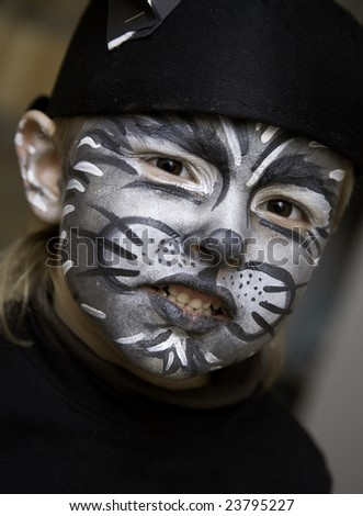 The boy makes a children's make-up, perhaps it is the cat - stock photo