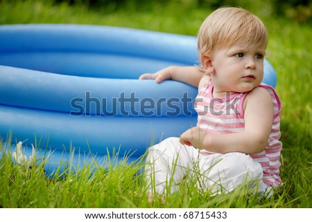 The boy next to pool. Year-old boy sitting on the grass and keeps the edge of an inflatable swimming pool - stock photo