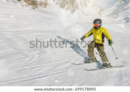 The boy on skis in mountains