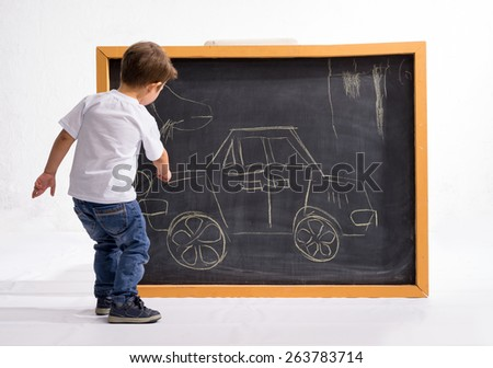 The boy on the blackboard painted car  - stock photo