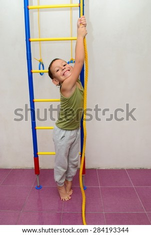 The boy on the swedish side is trying to climb a rope - stock photo