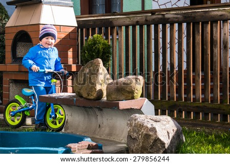 The boy playing with their first balance bike - stock photo