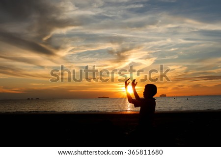 The boy praying at sunset on the beach.
