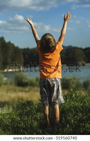 the boy raised his hands up nature - stock photo