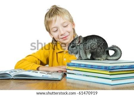 The boy reads books. Nearby a rodent a chinchilla