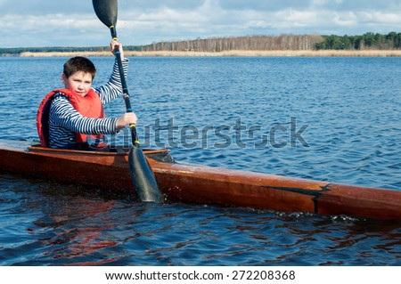 The boy rowing in a kayak on the river  - stock photo