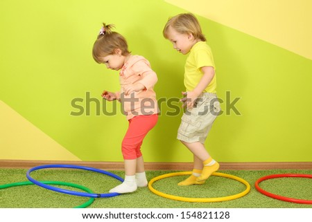 The boy runs after a girl in a bright room, on the floor are colored hoops - stock photo