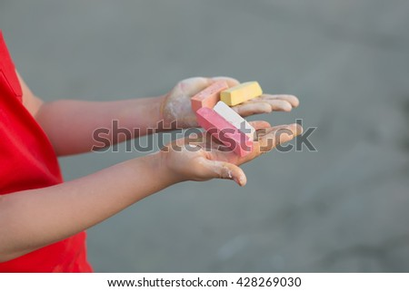 The boy's hands with multi-colored chalk - stock photo