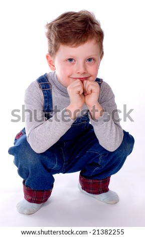 The boy sits and smiles on a white background - stock photo