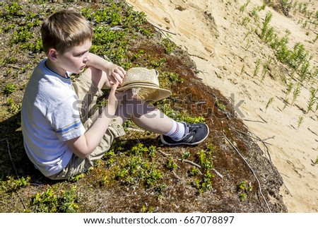 The boy sits on the edge of the sand cliff and Thinking about something