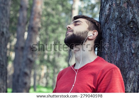The boy sits under a tree and listens to music - stock photo