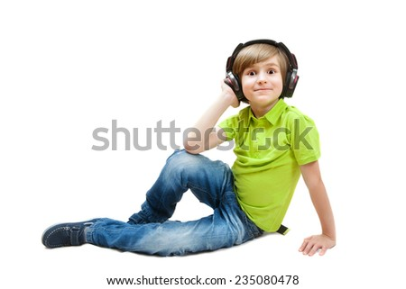 The boy sitting on the white floor listening to music