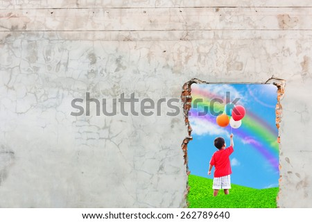 the boy standing on the green grass and hand hold bubble looking at rainbow on blue sky old brick wall background - stock photo