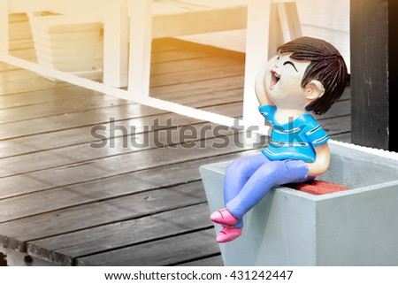 The boy stucco doll has smile on soft light background.