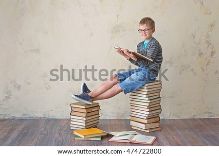 The boy student in sneakers shorts and a sweater sitting on a stack of books and reading. On a yellow colored background. Educational concept