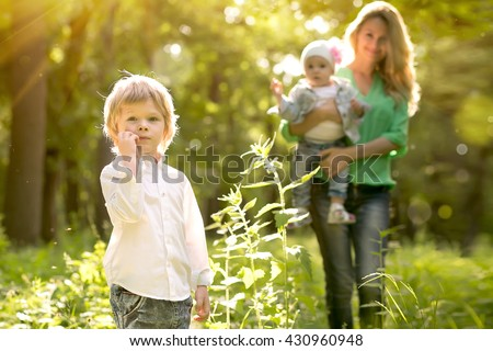 the boy the blonde with mother and the sister on a glade in forest part of park in the summer - stock photo