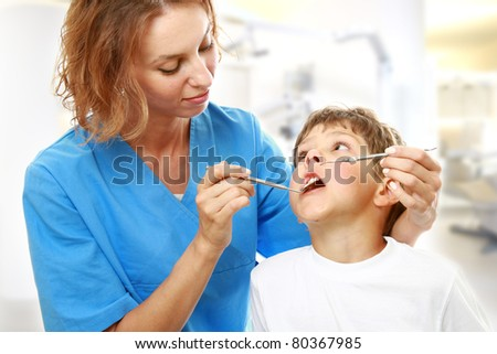 The boy with a doctor in a dental surgery.