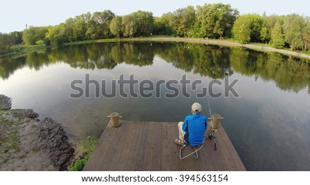 The boy with a fishing pole sitting on a wooden pier, aerial view - stock photo