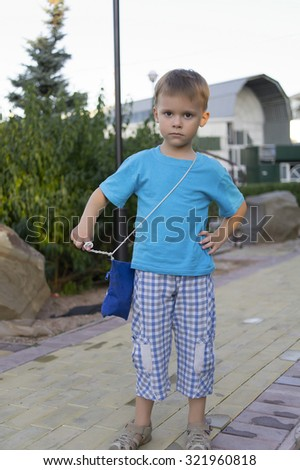 The boy with a strong-willed sight poses in park. - stock photo
