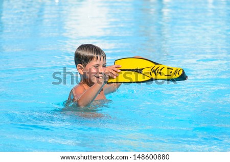 The boy with flippers for swimming in the pool.  - stock photo