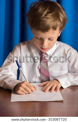 The boy writes with a ballpoint pen on a white sheet of paper