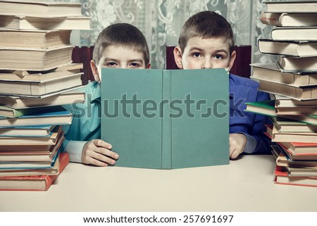 The boys are hiding behind the book. do not want to do homework