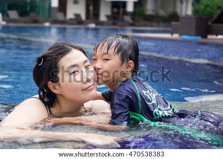 The boys kisses his mother at the swimming pool
