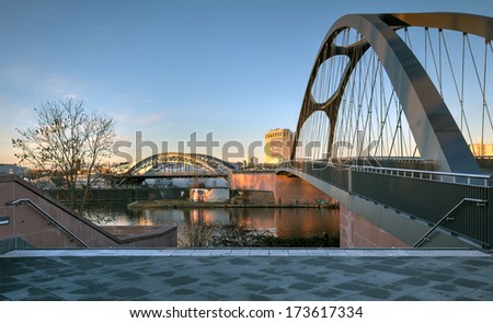 The brand new Osthafenbruecke (East Harbour Bridge) recently opened in Frankfurt, crossing the River Main with the renovated Honsellbruecke in the background. - stock photo