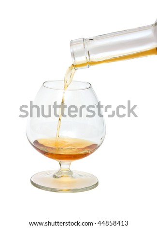 The brandy is flowing into the glass. Isolated. - stock photo