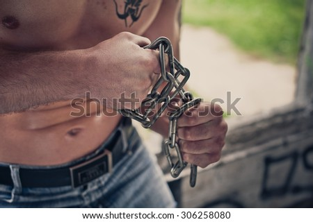 The brawny young man tears chains.
