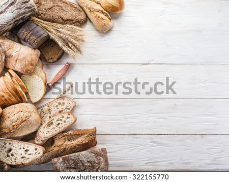 The bread and a wheat on the wooden desk. - stock photo