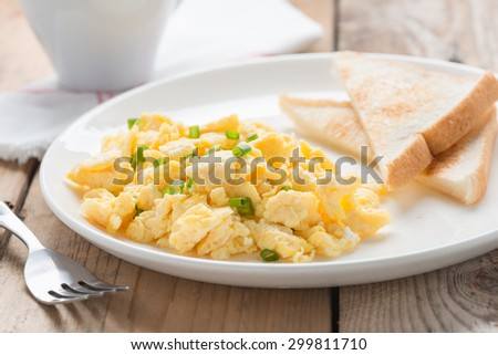 The breakfast with scrambled egg, toasts and coffee. - stock photo