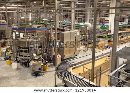 The brewery. The bottling of beer. Machine bottle labelling - stock photo