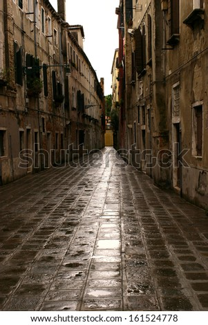The bricked alleyway sits between two buildings. - stock photo