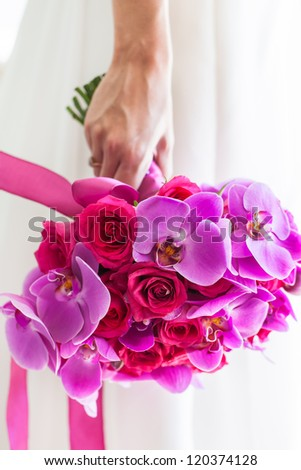 The bridal bouquet consist out of purple orchids and pink roses. - stock photo