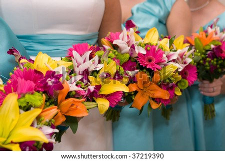 The bride and bridesmaids hold their colorful bridal flowers in a row.