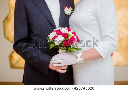 The bride and groom are holding a bouquet of roses.