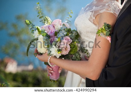 The bride and groom are holding wedding bouquet from roses, eucalyptus and dahlias, the bride is dressed in lace white wedding dress. - stock photo